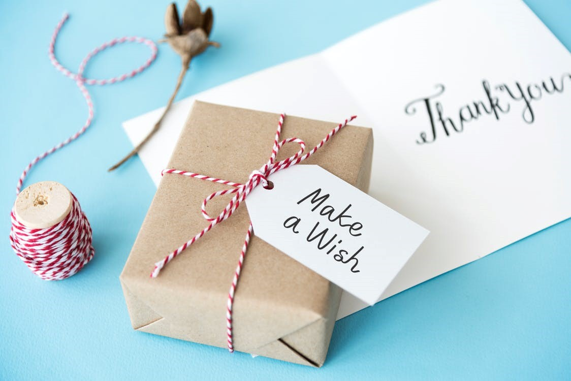 A brown gift box over a 'thank you' note